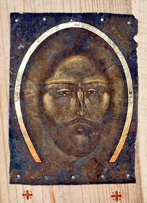 Ruostuneella metallilevyllä Jeesuksen kasvot.